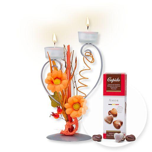 Teelichthalter mit orangefarbener Blumen-Deko und Pralinen-Herzen